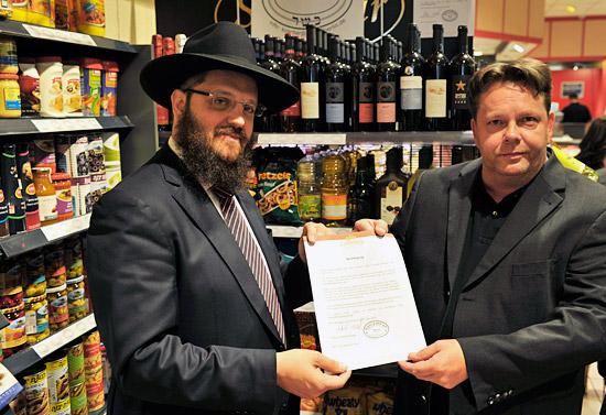 """Rabbiner Yehuda Teichtal überreicht """"Nah und Gut""""-Geschäftsführer Stefan Völker die Koscher-Zertifizierung der angebotenen koscheren Produkte. (© Matthias Hinrichsen)"""