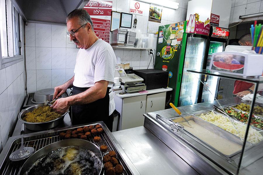 Ein original arabisches Familienrezept aus den 1950er-Jahren und frische Zutaten sind die Grundlage der besten Falafel in Haifa, sagt Alif Sbait, während der die Falafelmasse formt und in das heiße Fett plumpsen lässt. (© Matthias Hinrichsen)