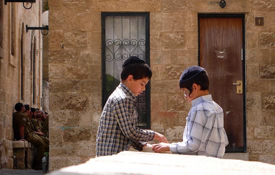 Kinder spielen unbedarft im jüdischen Viertel in der Jerusalemer Altstadt, während im Hintergrund die Soldaten präsent sind. (© Matthias Hinrichsen)