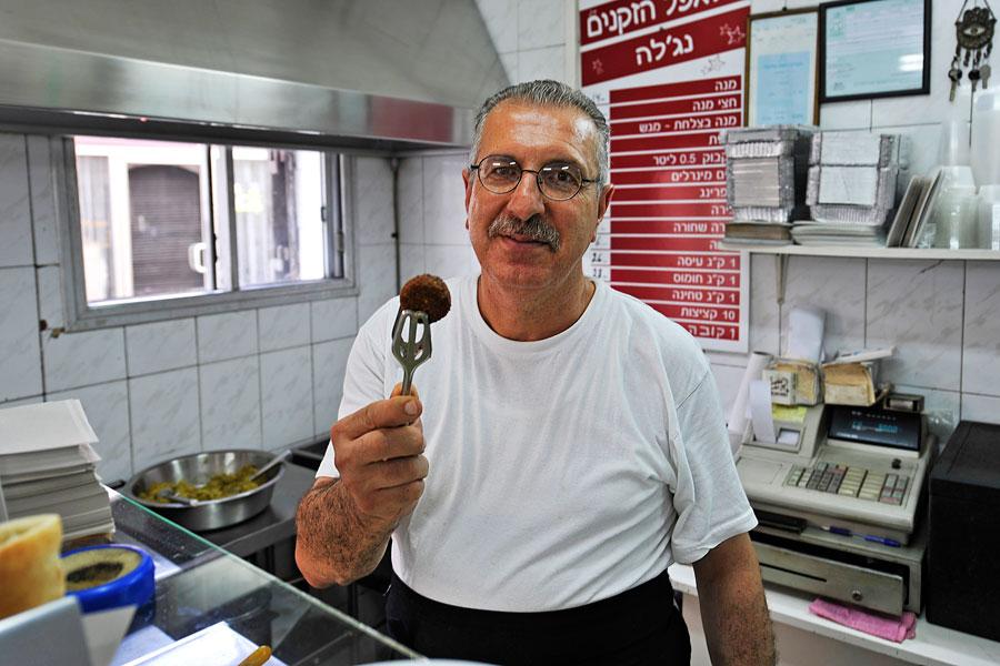 """""""So muss ein Falafel-Bällchen nach dem Frittieren aussehen"""", sagt Alif Sbait, der Bruder des Besitzers von Falafel HaZkenim. (© Matthias Hinrichsen)"""