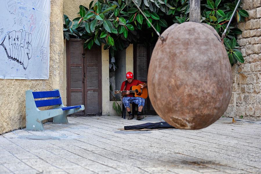 Ein Straßenmusiker nutzt die Berühmtheit des hängenden Oranger Suspendu und hofft auf ein paar Shekel von Touristen. (© Matthias Hinrichsen)