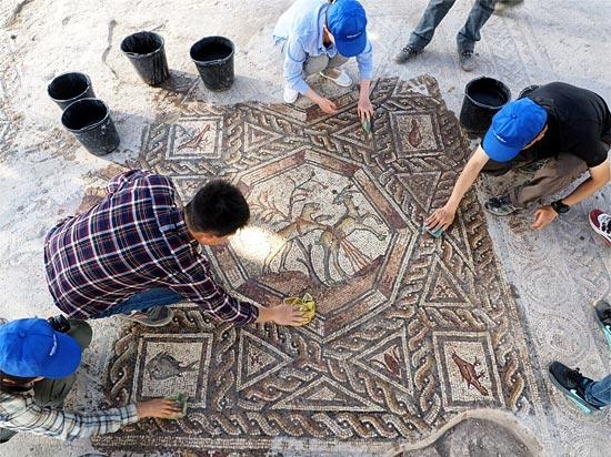 Mitarbeiter der Israelischen Altertumsbehörde reinigen den historischen Mosaikboden aus römischer Zeit. (© Assaf Peretz/Israel Antiquities Authority)