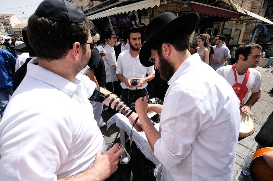 Freitags auf dem Mahane Yehuda Markt feiern orthodoxe Juden G-tt mit einem Minyan und binden dazu jedem Teilnehmer Tefillin. (© Matthias Hinrichsen)