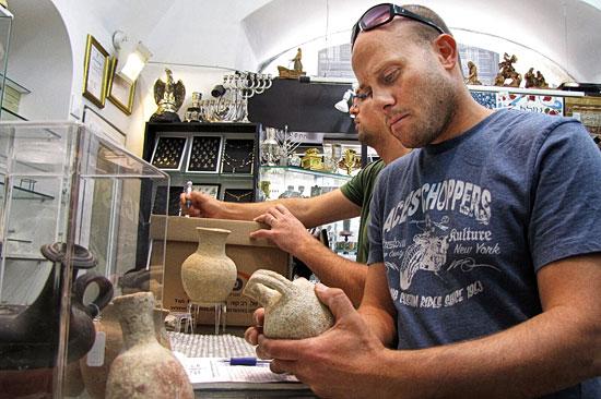 Inspektoren der israelische Altertumsbehörde beim Konfiszieren mutmaßlicher Raubgegenstände in dem Jerusalemer Souvenirgeschäft. (© Israelische Altertumsbehörde)