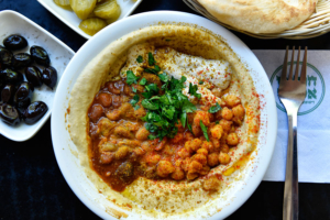 Jedes Restaurant serviert seine Hummus-Gerichte unterschiedlich - in dieser Variation mit Bohnen und Kichererbsen. (© Matthias Hinrichsen)
