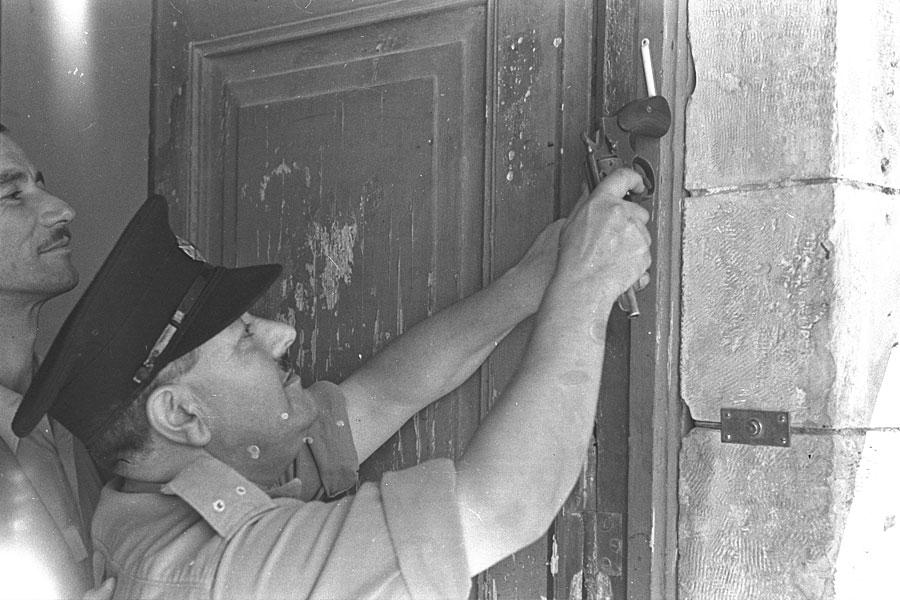 Ein jüdischer Polizist montiert 1948 mit einer Pistole eine Mezuza an einem Jerusalemer Gericht. (© GPO)