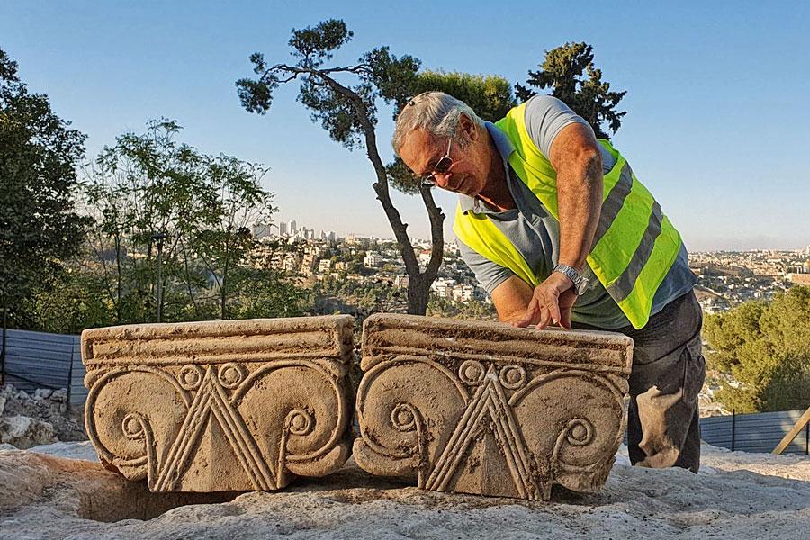 Yaakov Billig mit zwei Säulenkapitellen des Fundes.
